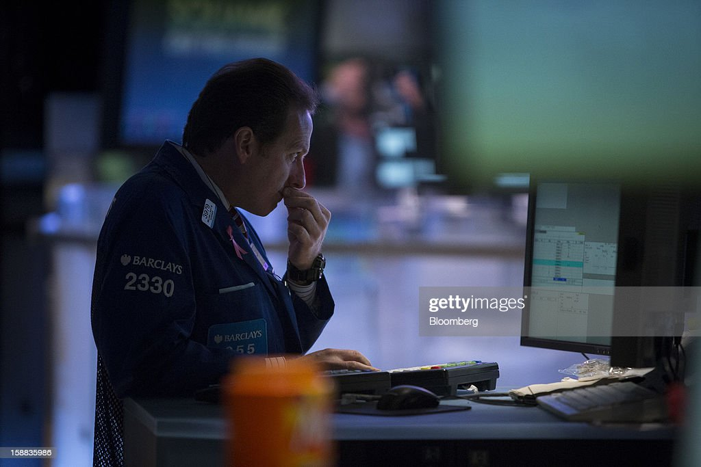 A trader works at the New York Stock Exchange (NYSE) in New York, U.S., on Monday, Dec. 31, 2012. Most U.S. stocks gained, rebounding from a five-day slump, as investors weighed prospects for a compromise in federal budget talks. Photographer: Scott Eells/Bloomberg via Getty Images