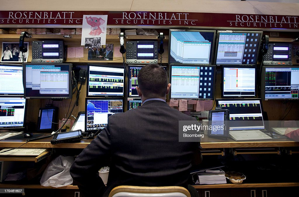 A trader works at the Rosenblatt Securities Inc. booth on the floor of the New York Stock Exchange (NYSE) in New York, U.S., on Thursday, June 13, 2013. U.S. stocks gained, ending a three-day decline in the Standard & Poors 500 Index, amid better-than-forecast economic data and acquisitions in the media and grocery industries. Photographer: Jin Lee/Bloomberg via Getty Images
