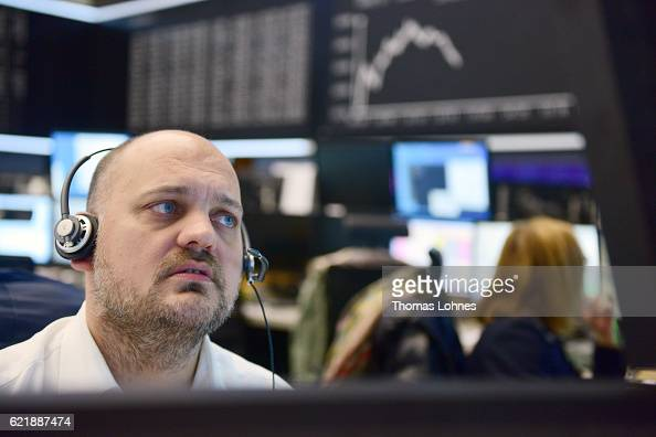 A trader works below the graph showing the day's course of the DAX index at the Frankfurt Stock Exchange on November 9 2016 in Frankfurt Germany...