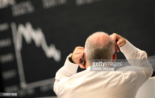 A trader works in front of a board displaying the chart of German share index DAX at the stock exchange in Frankfurt/M western Germany on November 2...