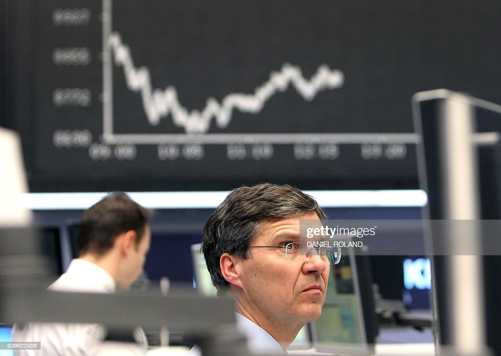 A trader works in front of a board displaying the chart of Germany's share index DAX at the stock exchange in Frankfurt am Main western Germany on...