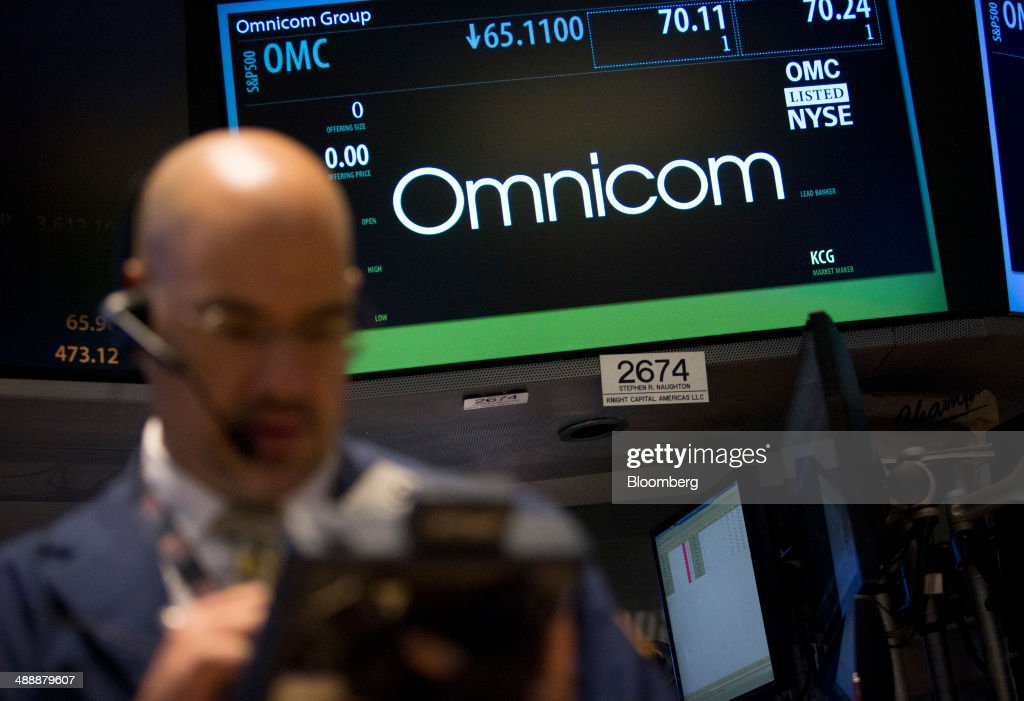 A trader works in front of a monitor displaying the Omnicom Group Inc., logo on the floor of the New York Stock Exchange (NYSE) in New York, U.S., on Monday, July 29, 2013. Omnicom Group Inc. and Publicis Groupe SA abandoned their $35 billion plan to create the worlds largest advertising company, saying they couldnt overcome obstacles that slowed progress toward the deals completion. Photographer: Scott Eells/Bloomberg via Getty Images