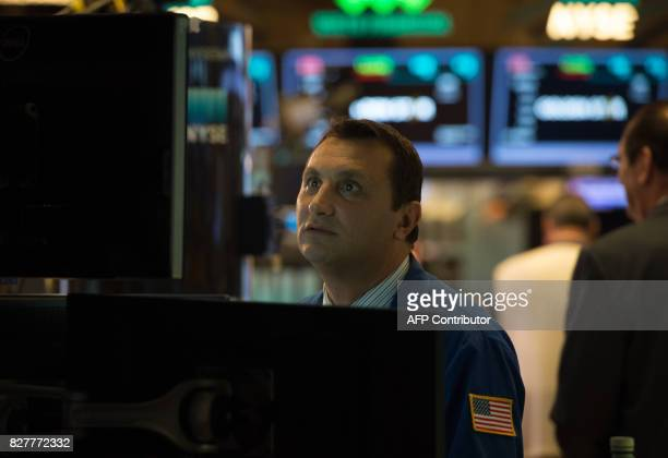 A trader works on the floor at the closing bell of the Dow Industrial Average at the New York Stock Exchange on August 8 2017 in New York Wall Street...