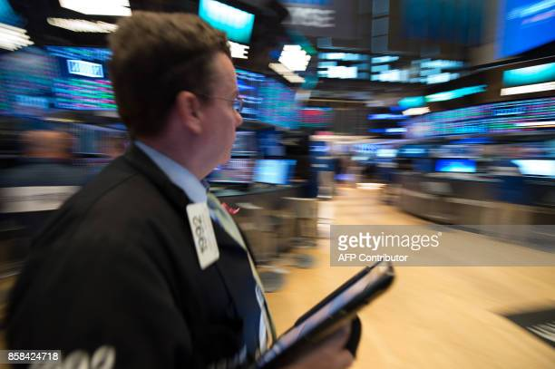A trader works on the floor at the closing bell of the Dow Industrial Average at the New York Stock Exchange on October 6 2017 in New York Wall...