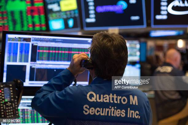 A trader works on the floor at the closing bell of the Dow Industrial Average at the New York Stock Exchange on October 13 2017 in New York / AFP...