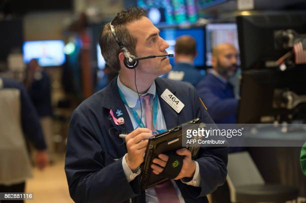 A trader works on the floor at the closing bell of the Dow Industrial Average at the New York Stock Exchange on October 18 2017 in New York The Dow...