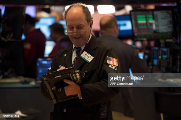 A trader works on the floor at the closing bell of the Dow Jones Industrial Average at the New York Stock Exchange on September 28 2017 in New York /...