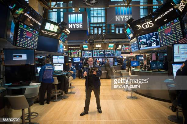 A trader works on the floor before the Dow Jones closing bell at the New York Stock Exchange January 31 2017 in New York The Dow retreated Tuesday as...