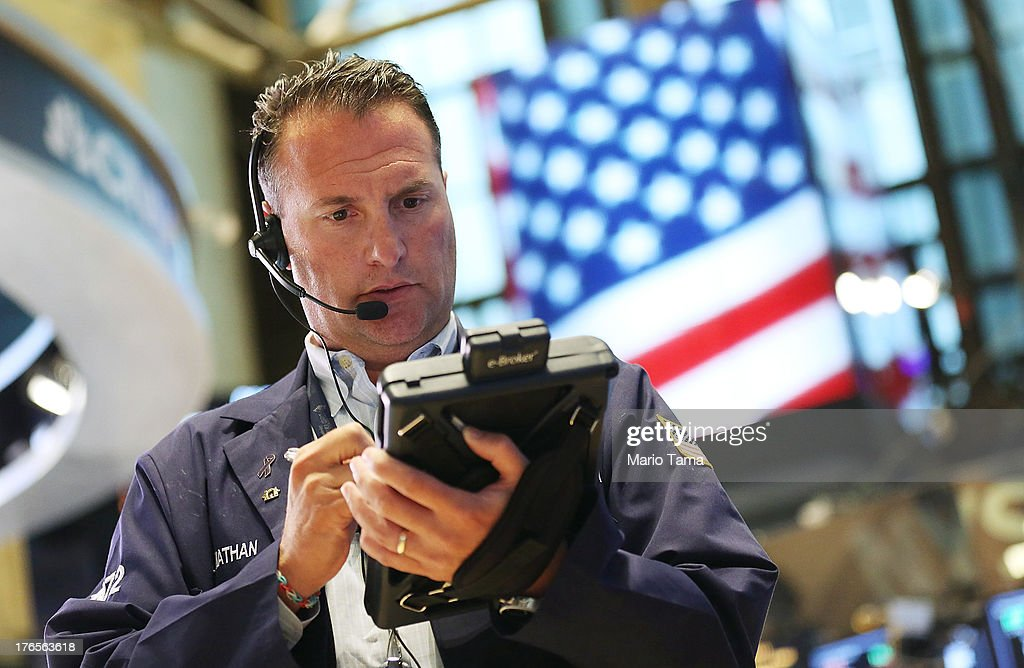 A trader works on the floor of the New York Stock Exchange after the closing bell on August 15, 2013 in New York City. Stocks dropped on weak earnings as the Dow fell 225 points to close at 15,112.19.