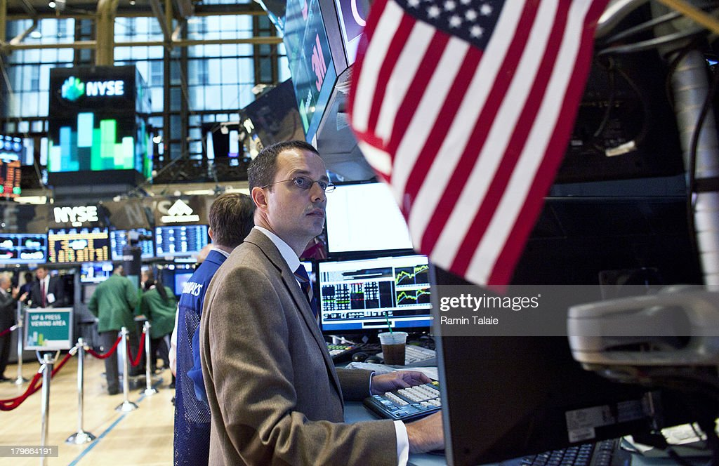 A trader works on the floor of the New York Stock Exchange (NYSE) after the opening bell on September 6, 2013 in New York City. A group of National Hokey League all stars rang the opening bell in celebration of the start of upcoming 2013-14 season featuring six outdoor hockey games.