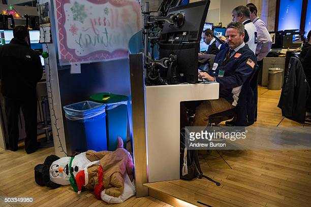 A trader works on the floor of the New York Stock Exchange as holiday decorations are left on the ground during the morning of January 4 2016 in New...