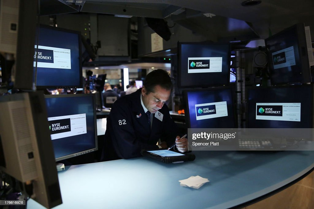 A trader works on the floor of the New York Stock exchange (NYSE) during early trading on August 16, 2013 in New York City. Following a day of large stock market losses, the The Dow Jones industrial average was up slightly in morning trading.