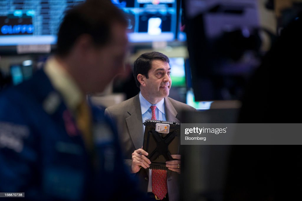 A trader works on the floor of the New York Stock Exchange (NYSE) in New York, U.S., on Wednesday, Jan. 2, 2013. U.S. stocks rose, after the largest year-end rally for the Standard & Poor's 500 Index since 1974, as lawmakers passed a bill averting spending cuts and tax increases threatening a recovery in the world's biggest economy. Photographer: Scott Eells/Bloomberg via Getty Images