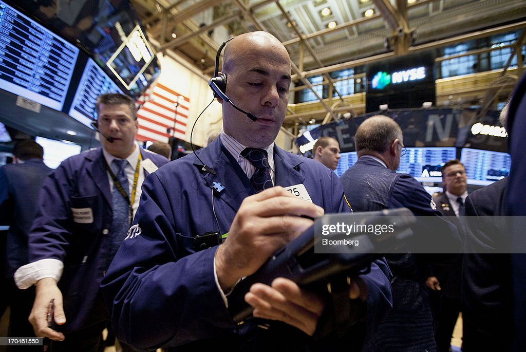 A trader works on the floor of the New York Stock Exchange (NYSE) in New York, U.S., on Thursday, June 13, 2013. U.S. stocks gained, ending a three-day decline in the Standard & Poors 500 Index, amid better-than-forecast economic data and acquisitions in the media and grocery industries. Photographer: Jin Lee/Bloomberg via Getty Images