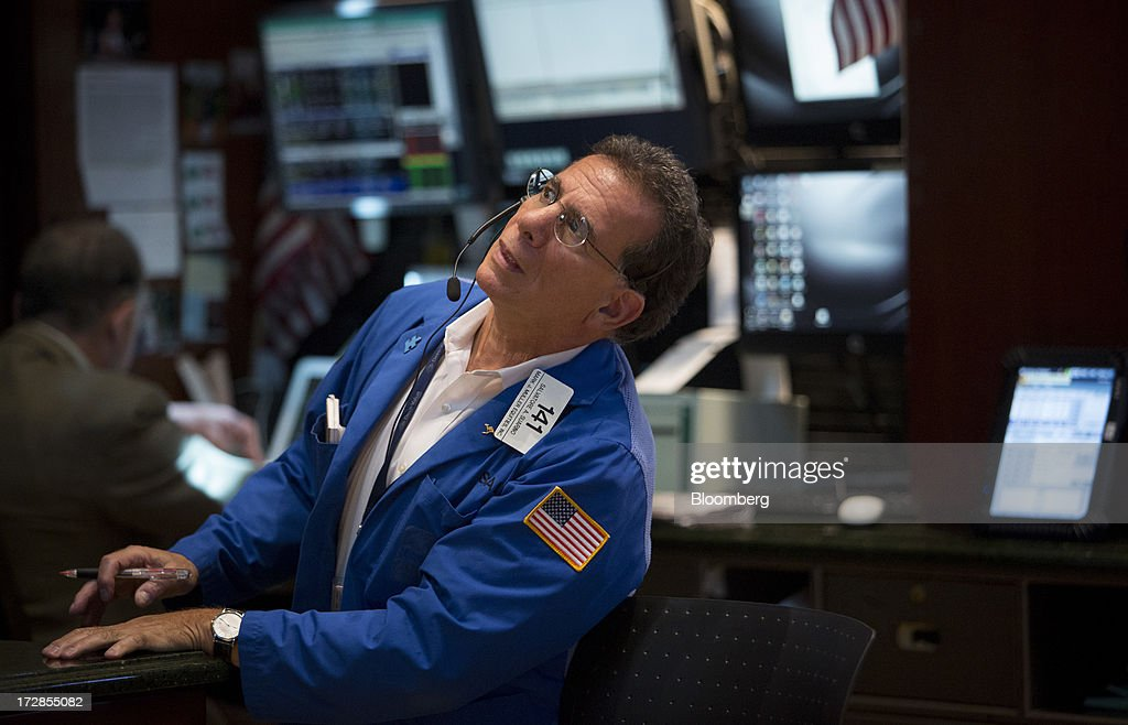 A trader works on the floor of the New York Stock Exchange (NYSE) in New York, U.S., on Friday, July 5, 2013. U.S. stocks fluctuated between gains and losses as faster-than-forecast jobs growth fueled bets the Federal Reserve will begin to reduce its bond buying. Photographer: Scott Eells/Bloomberg via Getty Images
