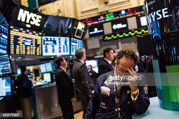 A trader works on the floor of the New York Stock Exchange on December 4 2013 in New York City The Dow Jones Industrial Average dipped over 100...