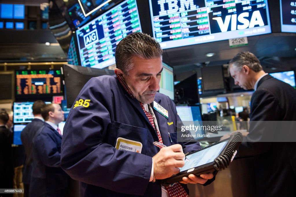 A trader works on the floor of the New York Stock Exchange (NYSE) on the morning of January 30, 2014 in New York City. The NYSE welcomed members of the Super Bowl Host Committee, owners and managers of the Denver Broncos and Seattle Seahawks to ring the opening bell today.