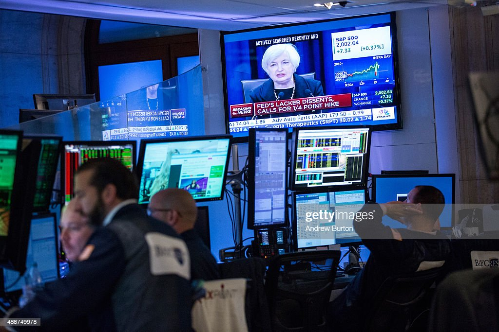 A trader works on the floor of the New York Stock Exchange while Federal Reserve Chairwoman Janet Yellen explains why the Federal Reserve chose not...