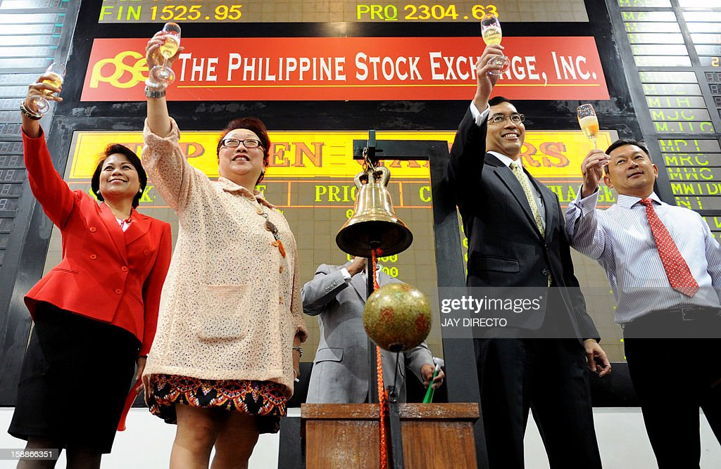 Traders and officials of the Philippine Stock Exchange make a toast in front of the electronic board during the opening of the first day of trading in Manila on January 2, 2013. Philippine share prices closed 0.83 percent higher, up 48.26 points to close at 5,860.99, to a new all-time high on rising optimism that the US fiscal cliff would be averted, dealers said.