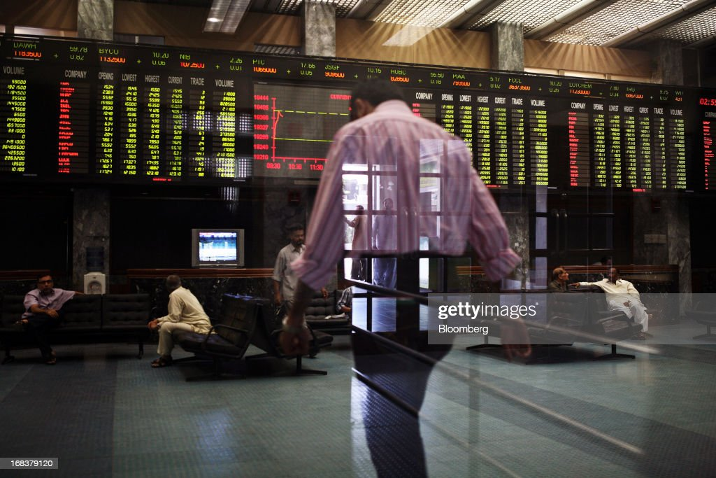 Traders are seen through reflected glass in the the Karachi Stock Exchange in Karachi, Pakistan, on Wednesday, May 8, 2013. Pakistan is to hold parliamentary elections on May 11. According to opinion polls, Nawaz Sharif of the Pakistan Muslim League-N (PMLN), leads Imran Khan of Pakistan Tehrik-e-Insaf (PTI) in the race to replace president Asif Ali Zadari and become Pakistan's 12th president. Photographer: Asim Hafeez/Bloomber