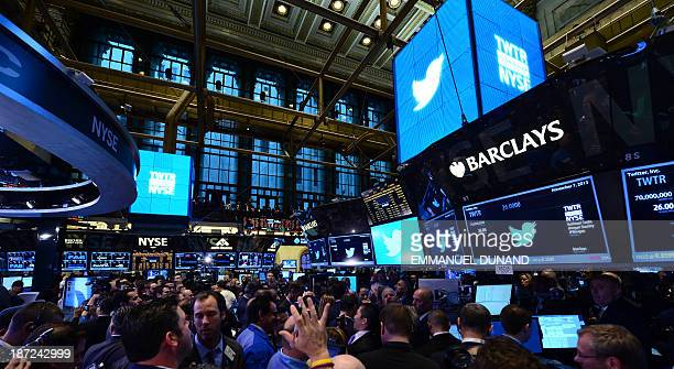 Traders are shown with the logo of Twitter and the symbol on which Twitter's stock will be traded on the floor of the New York Stock Exchange on...