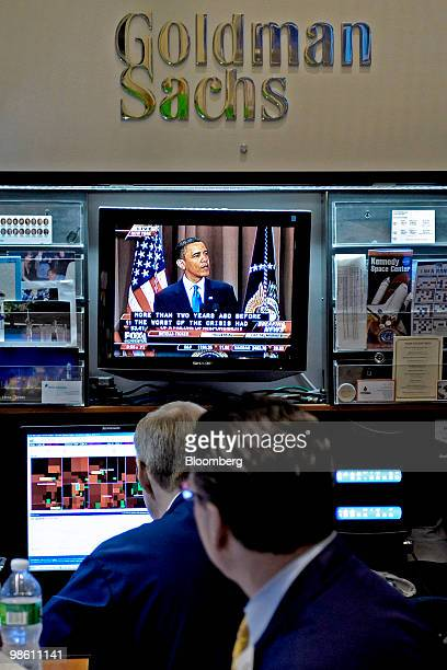 Traders at the Goldman Sachs Group Inc booth on the floor of the New York Stock Exchange watch a live broadcast of President Barack Obama speaking...