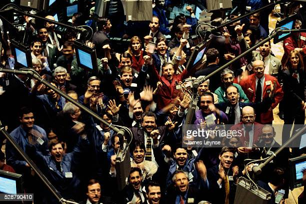 Traders celebrate at the end of the day from the New York Stock Exchange trading floor where the Dow closed at 99967