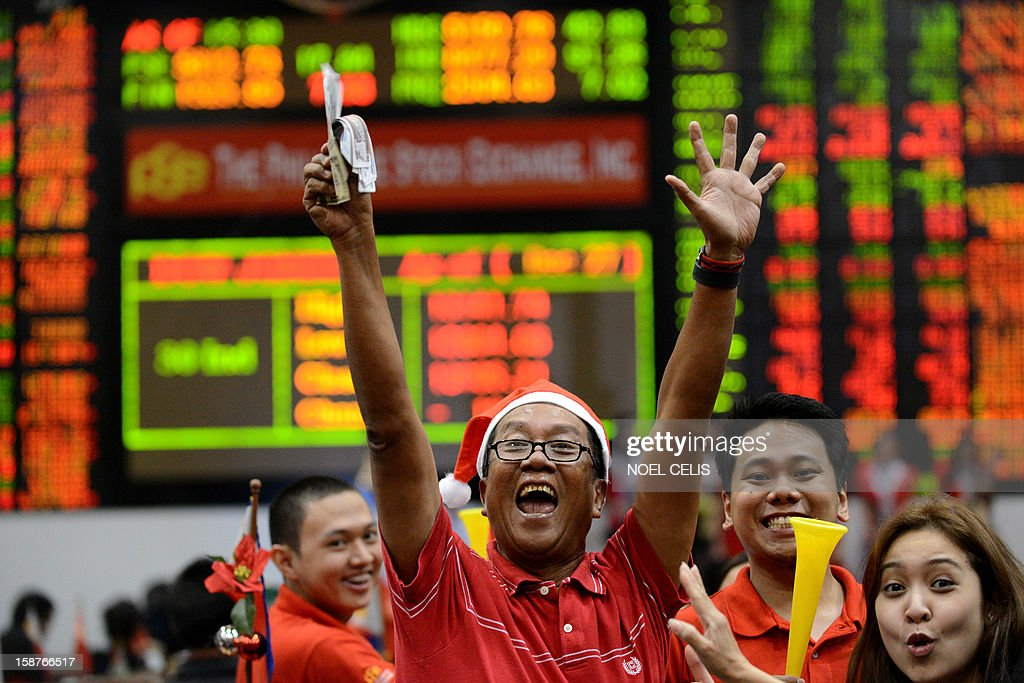 Traders celebrate during the closing ceremony of the 2012 trading year at the Philippines Stock Exchange in Manila on December 28, 2012. Asian shares rose on December 28 on hopes of a last-minute deal to avert the US fiscal cliff, despite warnings from a leading Democrat that an agreement is unlikely just days before a year-end deadline.
