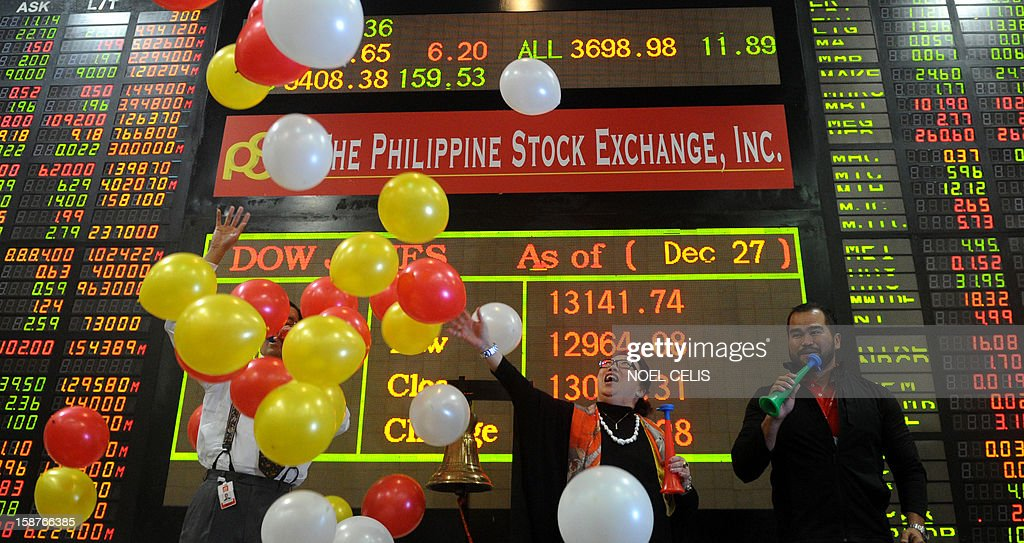 Traders celebrate during the closing ceremony of the 2012 trading year in front of an electronic board at the Philippines Stock Exchange in Manila on December 28, 2012. Asian shares rose on December 28 on hopes of a last-minute deal to avert the US fiscal cliff, despite warnings from a leading Democrat that an agreement is unlikely just days before a year-end deadline. AFP PHOTO / NOEL CELIS