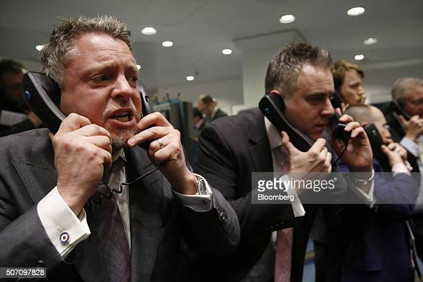 Traders clerks and brokers react as they speak on telephones on the trading floor of the open outcry pit at the London Metal Exchange on the last day...