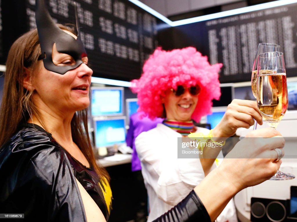 Traders dressed in a Batman costume, left, and a hippie with a pink wig raise a toast to celebrate Carnival Tuesday while on the floor of the Frankfurt Stock Exchange in Frankfurt, Germany, on Tuesday, Feb. 12, 2013. Traders wear costumes as part of a long-standing tradition in honor of Germany's Carnival festivities. Photographer: Ralph Orlowski/Bloomberg via Getty Images
