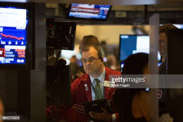 Traders finish the day at the New York Stock Exchange after markets took a sharp turn downward after news reports of former FBI Director James...