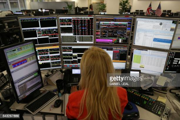 Traders from ETX Capital work in central london on June 27 2016 Shares in banks airlines and property companies plunged on the London stock exchange...