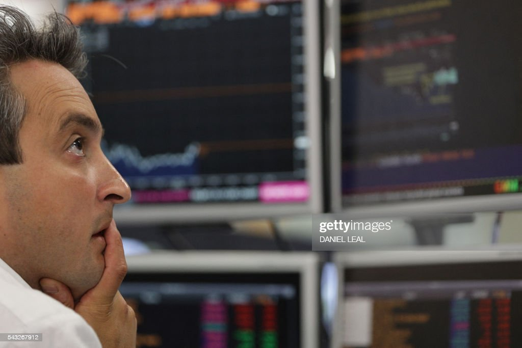 Traders from ETX Capital work in central london on June 27, 2015. Shares in banks, airlines and property companies plunged on the London stock exchange Monday as investors singled out the three sectors as being the most vulnerable to Britain's decision to leave the EU. / AFP / Daniel Leal-Olivas