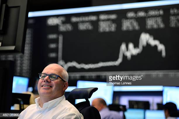 A traders looks to his monitors in front of the index board that shows the DAX has broken the 10000 mark for the first time ever at the Deutsche...