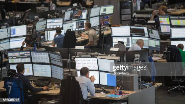 Traders monitor data on banks of desktop computer monitors on the RWE AG energy trading floor in Essen Germany on Wednesday Aug 16 2017 RWE plans to...