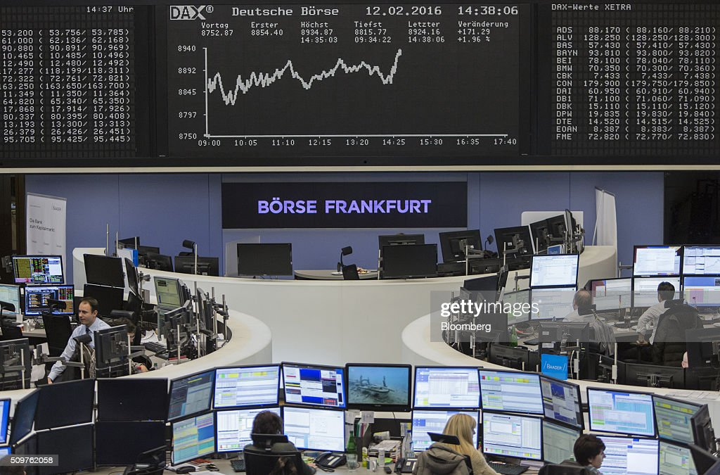 Traders monitor financial data as the DAX Index curve sits displayed on an electronic board inside the Frankfurt stock exchange in Frankfurt, Germany, on Friday, Feb. 12, 2016. A rebound in banks helped lift European stocks from their lowest levels since 2013, trimming a second weekly decline. Photographer: Martin Leissl/Bloomberg via Getty Images