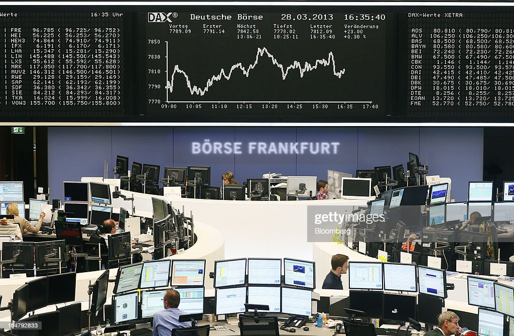 Traders monitor financial data on computer screens beneath a display of the DAX Index curve at the Frankfurt Stock Exchange in Frankfurt, Germany, on Thursday, March 28, 2013. Cyprus's lenders had been closed since March 16, when the European Union presented a proposal to force losses on all depositors in exchange for a 10 billion-euro bailout. Photographer: Ralph Orlowski/Bloomberg via Getty Images
