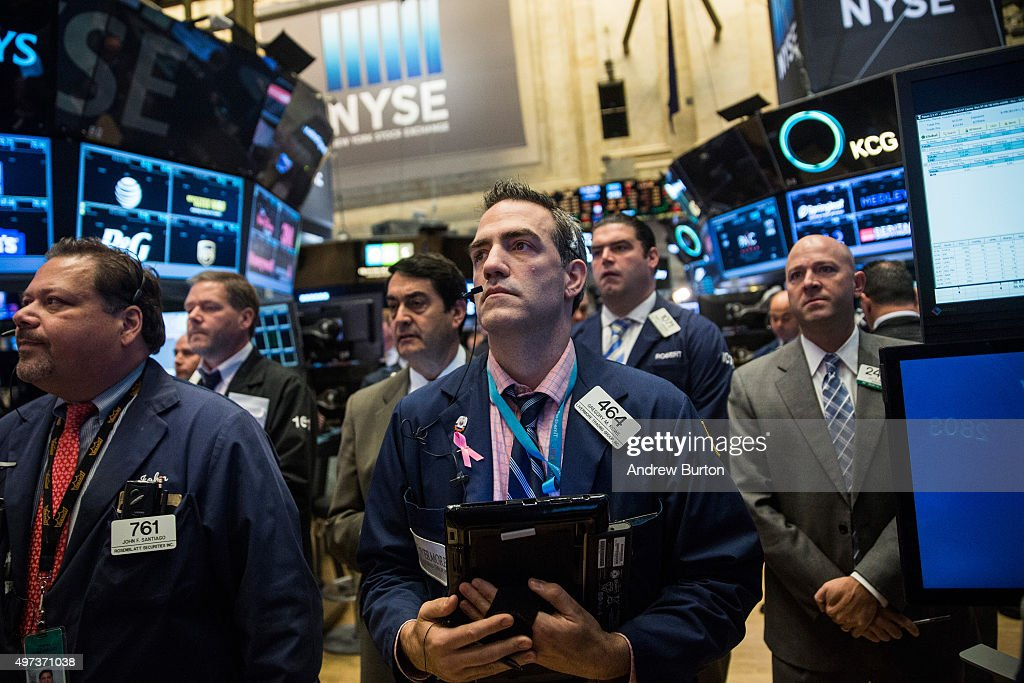 Traders on the floor of the New York Stock Exchange participate in a moment of silence in honor of the victims of the terrorist attacks in Paris last...