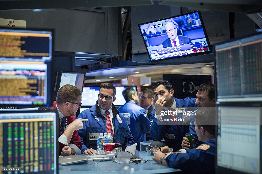 Traders on the floor of the New York Stock Exchange wait to learn if the Federal Reserve will raise interest rates during the afternoon of January 27...