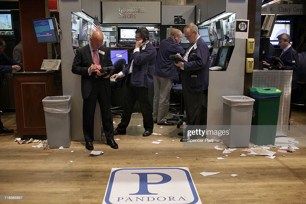 Traders on the floor of the New York Stock Exchange walk stand in front of insignia for Pandora Media Inc., the online-radio company, on its first day of trading as a public company on June 15, 2011 in New York City. Pandora stock rose as much as 63 percent to $26 following its debut on the New York Stock Exchange, under the symbol P. Reversing much of the previous day's gains, stocks fell Wednesday as more news emerged about the fragility of the American and global economy. The Dow Jones Industrial Average fell 88 points, or 0.8%, to 11987 in morning trading.