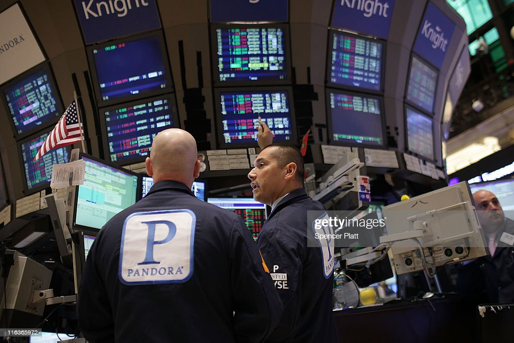 Traders on the floor of the New York Stock Exchange walk wear an insignia for Pandora Media Inc., the online-radio company, on its first day of trading as a public company on June 15, 2011 in New York City. Pandora stock rose as much as 63 percent to $26 following its debut on the New York Stock Exchange, under the symbol P. Reversing much of the previous day's gains, stocks fell Wednesday as more news emerged about the fragility of the American and global economy. The Dow Jones Industrial Average fell 88 points, or 0.8%, to 11987 in morning trading.