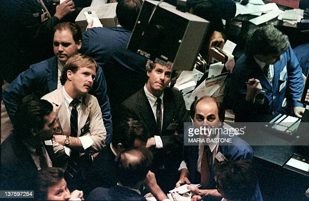 Traders on the New York Stock Exchange look at stock rates 19 October 1987 as stocks were devastated during one of the most frantic days in the...