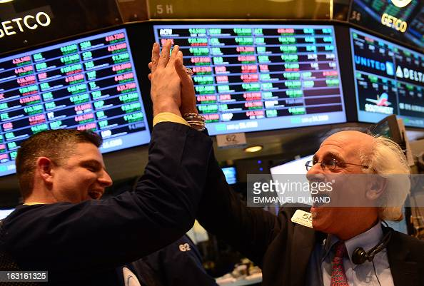 Traders react at the end of trade at the New York Stock Exchange in New York March 5 2013 The Dow Jones industrial average surged to a record high at...