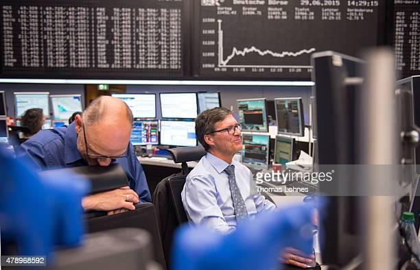 Traders react under the day's performance graph showing a sharp drop of the German DAX stock market index early today and a partial recovery later on...