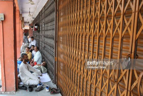 Traders rest outside their shuttered shops during the nationwide shutdown to protest GST at Kishanpole Bazar on June 30 2017 in Jaipur India The...