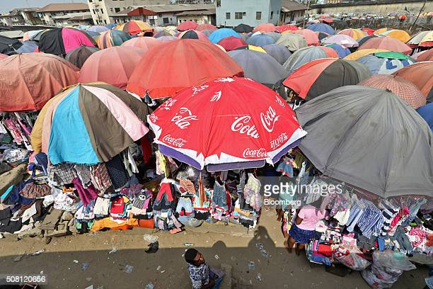 Traders sell their goods beneath large parasols including one decorated with CocaCola Co logos at the Mile One open market in Port Harcourt Nigeria...