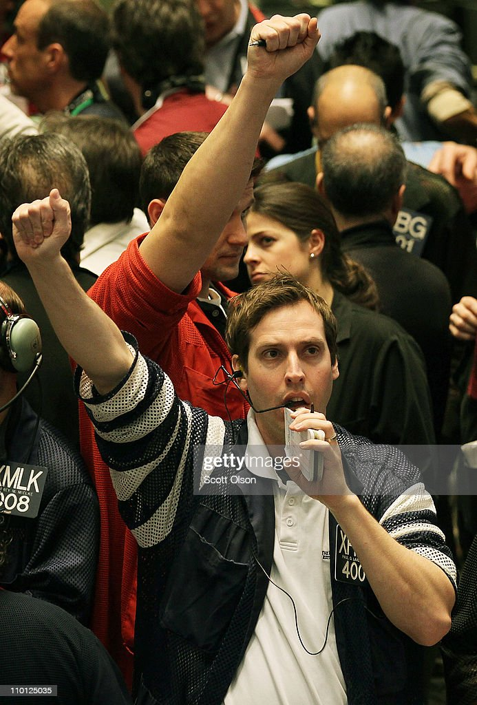 Traders signal offers in the S&P 500 stock index futures pit at the CME Group following the announcement by the Federal Open Market Committee (FOMC) that it would maintain the key policy rate near zero on March 15, 2011 in Chicago, Illinois. U.S. stock and commodity prices tumbled today following a sharp drop in Japan's stock market, as investors worldwide worry about the economic impact of that country's recent earthquake, tsunami and unfolding nuclear crisis.