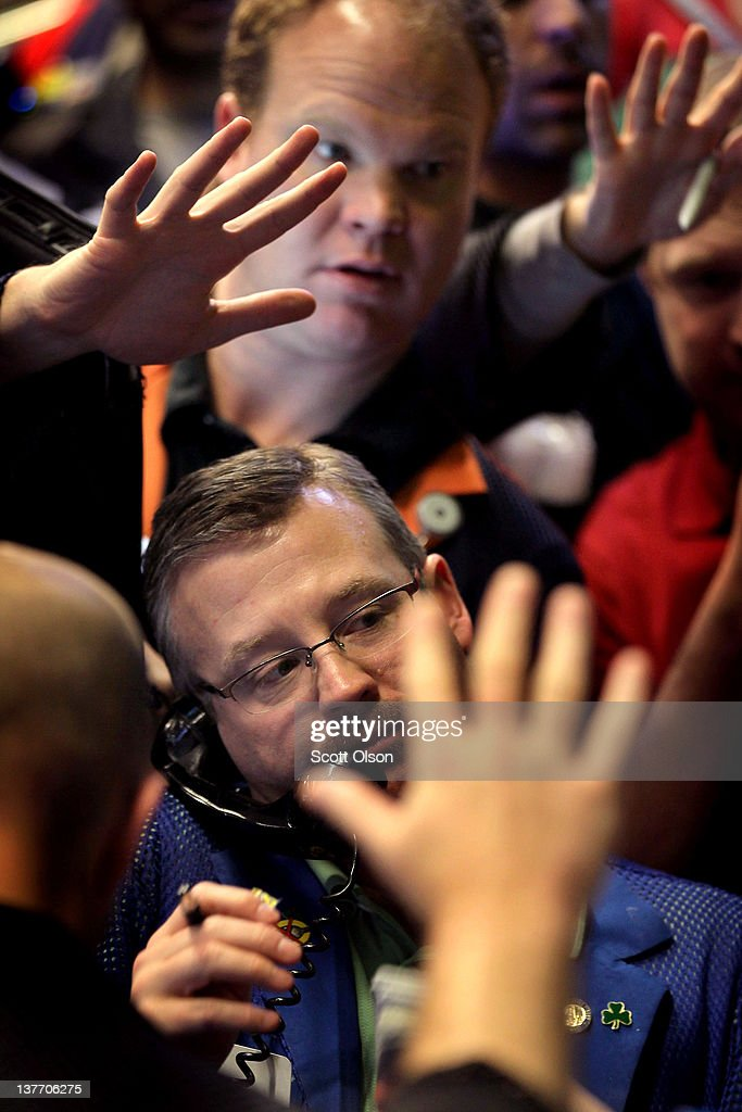 Traders signal offers in the Standard & Poor's 500 stock index options pit at the Chicago Board Options Exchange (CBOE) following the Federal Open Market Committee meeting on January 25, 2012 in Chicago, Illinois. Following the meeting the Fed, which left interest rates unchanged, said it does not plan any rate changes until late 2014.