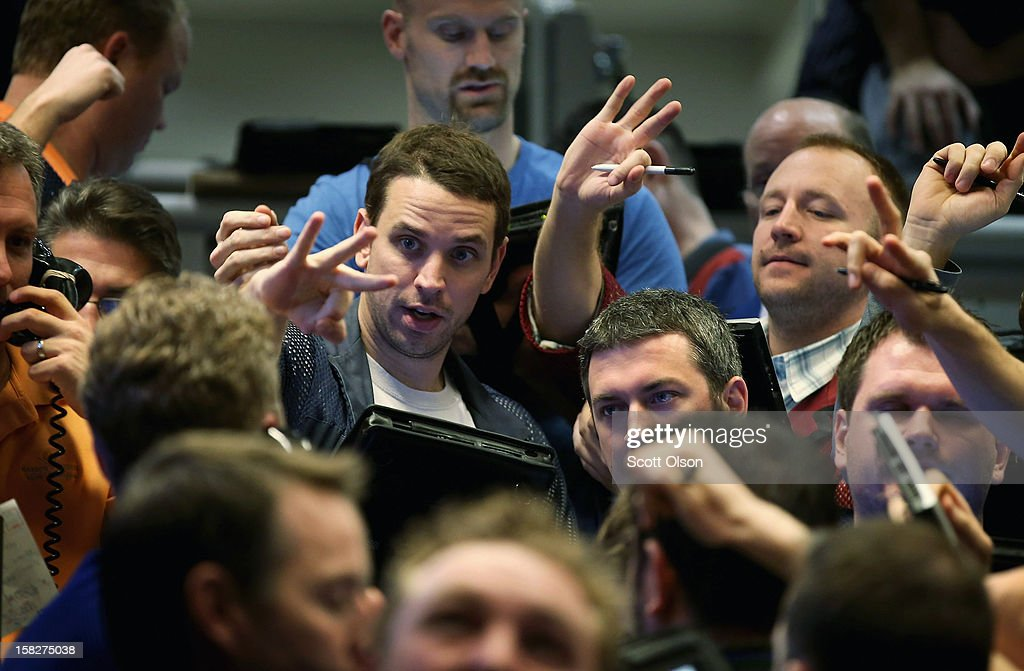 Traders signal offers in the Standard & Poor's 500 stock index options pit at the Chicago Board Options Exchange (CBOE) following the Federal Open Market Committee meeting on December 12, 2012 in Chicago, Illinois. The Fed announced today that they expect to keep a key short-term interest rates at or near zero percent as long as the unemployment rate remains above 6.5 percent. William Brodsky, Chairman and CEO of the CBOE, said that he will step down as CEO following the 2013 Annual Meeting.